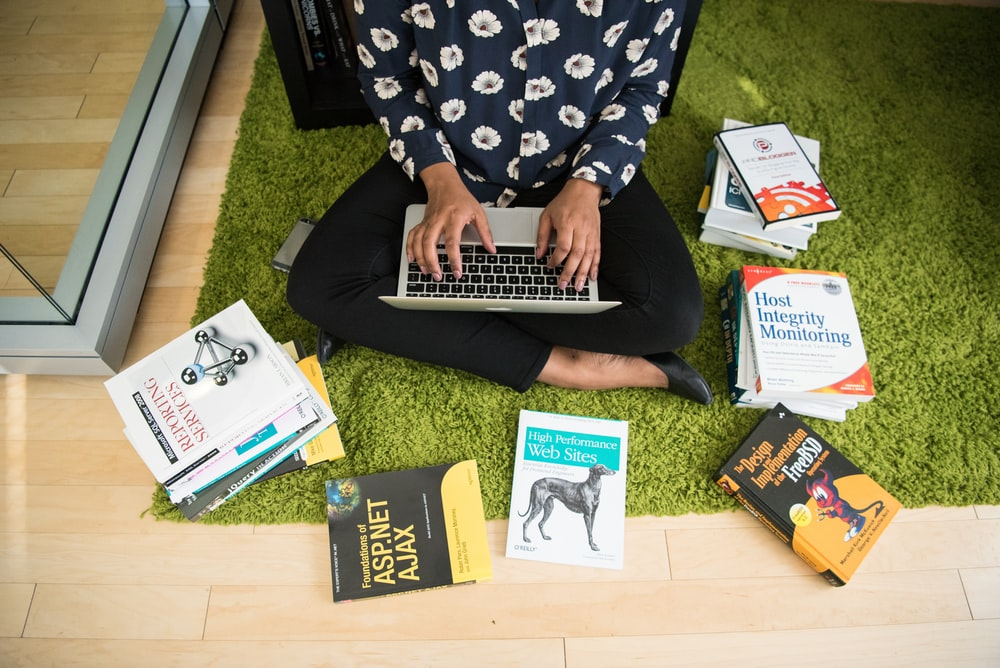 woman using laptop sitting on carpet surrounded with books