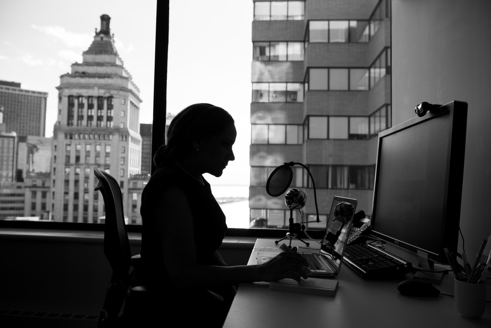 grayscale photography of woman sitting in front of a computer