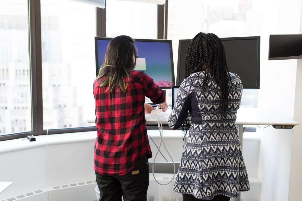 two women standing in front of two black monitors