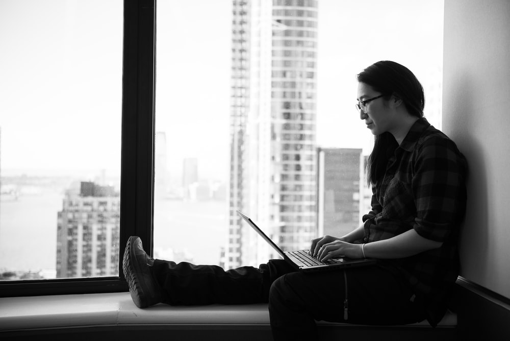 grayscale photography of woman facing laptop computer