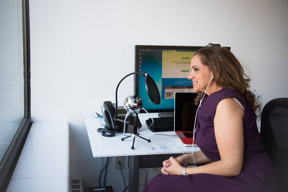 woman talking in front of a pop filter