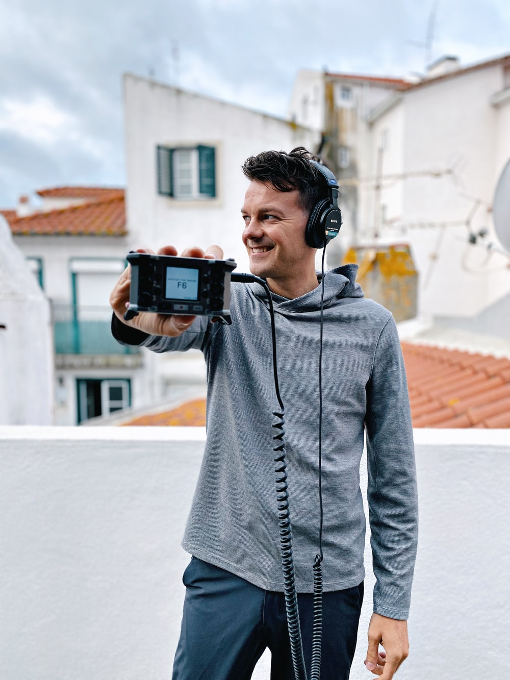 man holding smartphone and wearing headset