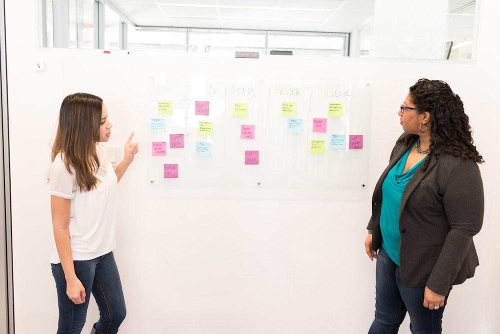 two women standing beside white board
