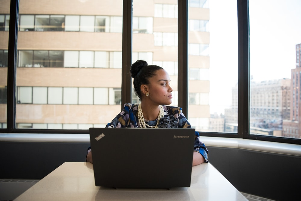 woman sitting on chair front of black Lenovo laptop