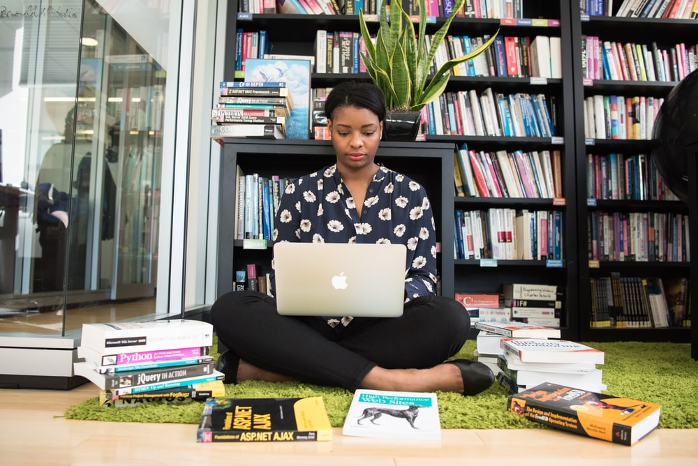 woman sitting down surrounded by books while using MacBook