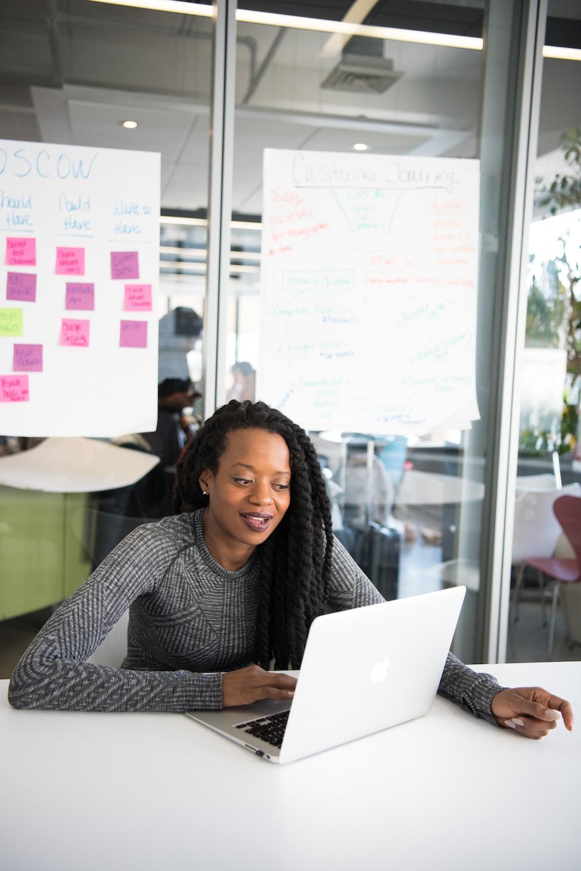 shallow focus photo of woman using gray laptop computer