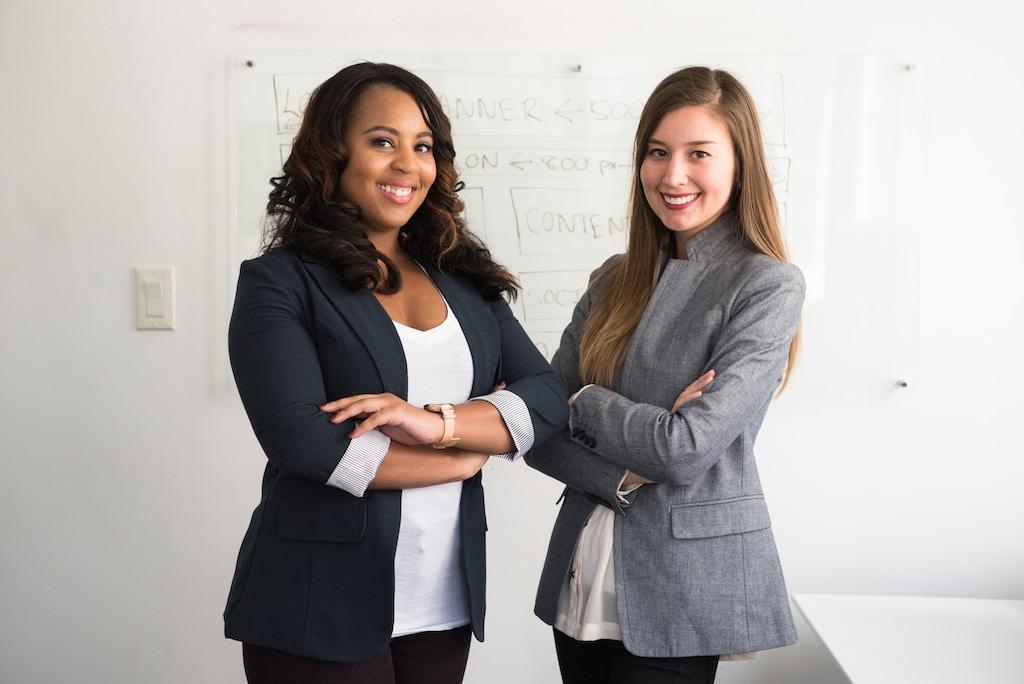 Mulheres emprendedoras. Na foto estão duas mulheres com blazer braços entrelaçados olhando para foto.
