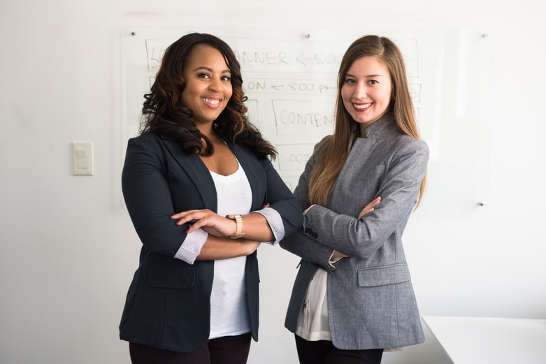 two women in suits standing beside wall
