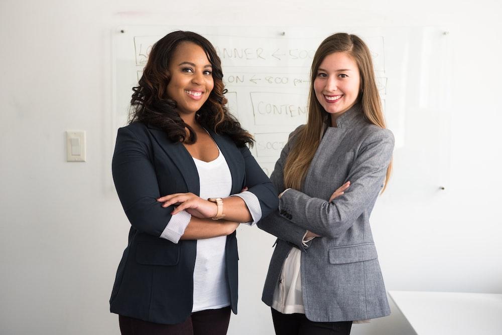 壁の横に立っているスーツの2人の女性