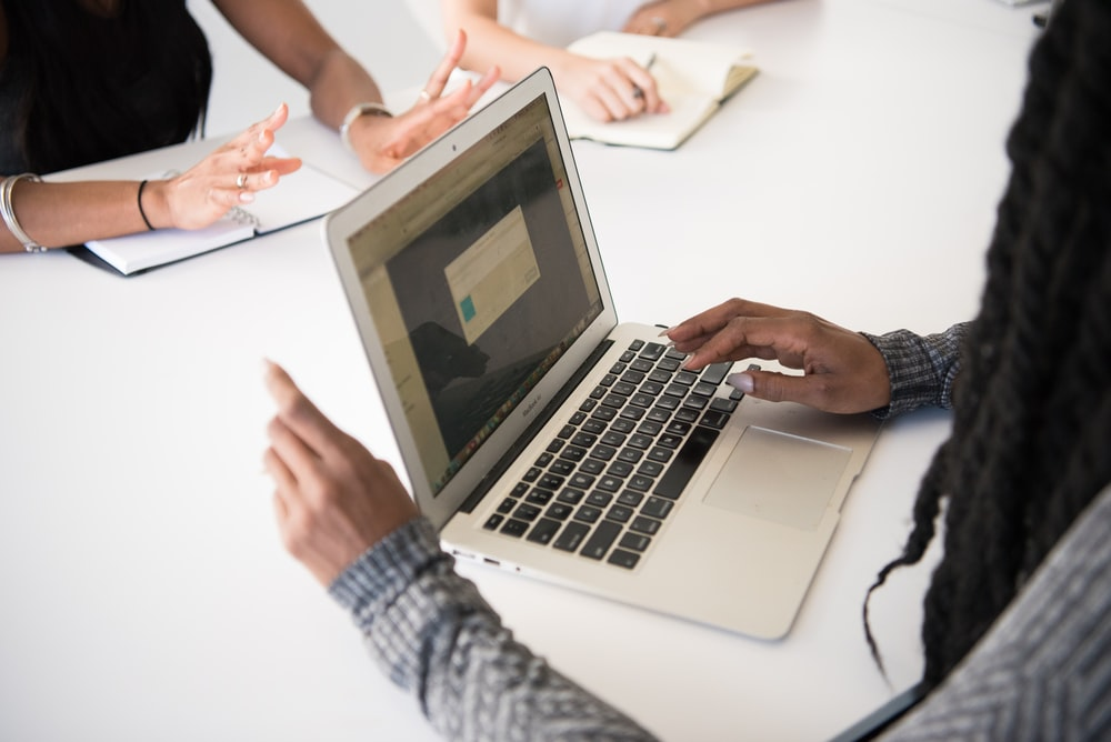 person using MacBook Air at the table