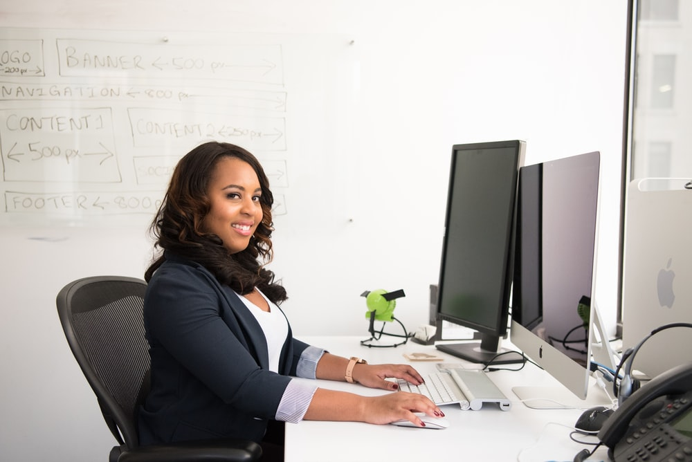 shallow focus photo of woman in black jacket using iMac