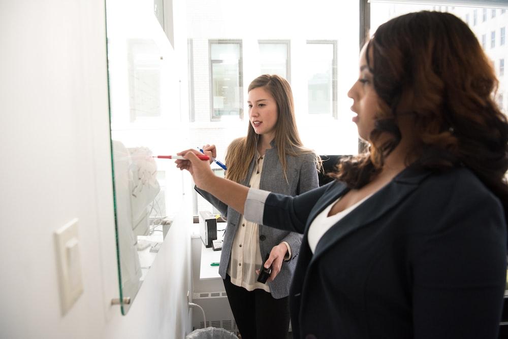 two women writing on glass panel