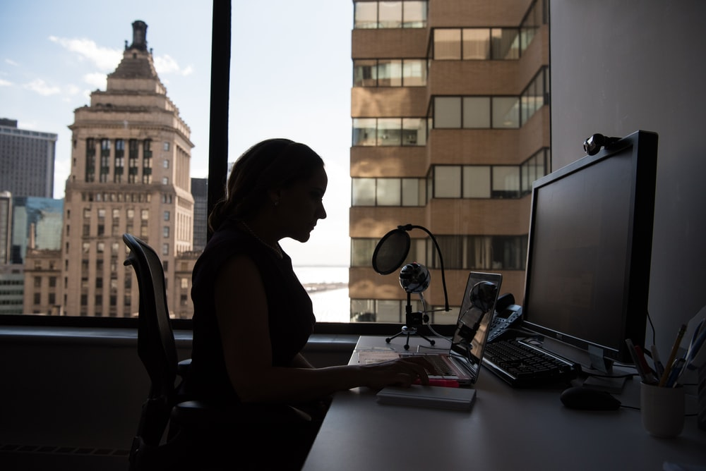 woman sitting in front of desk with computer monitor and keyboard on top