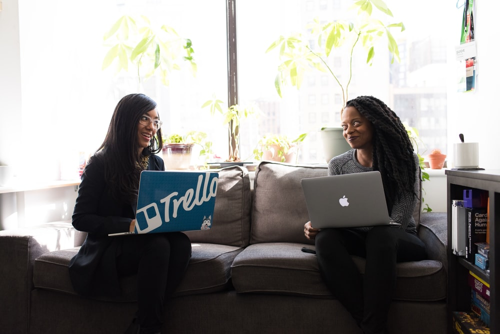 two women with laptop on laps