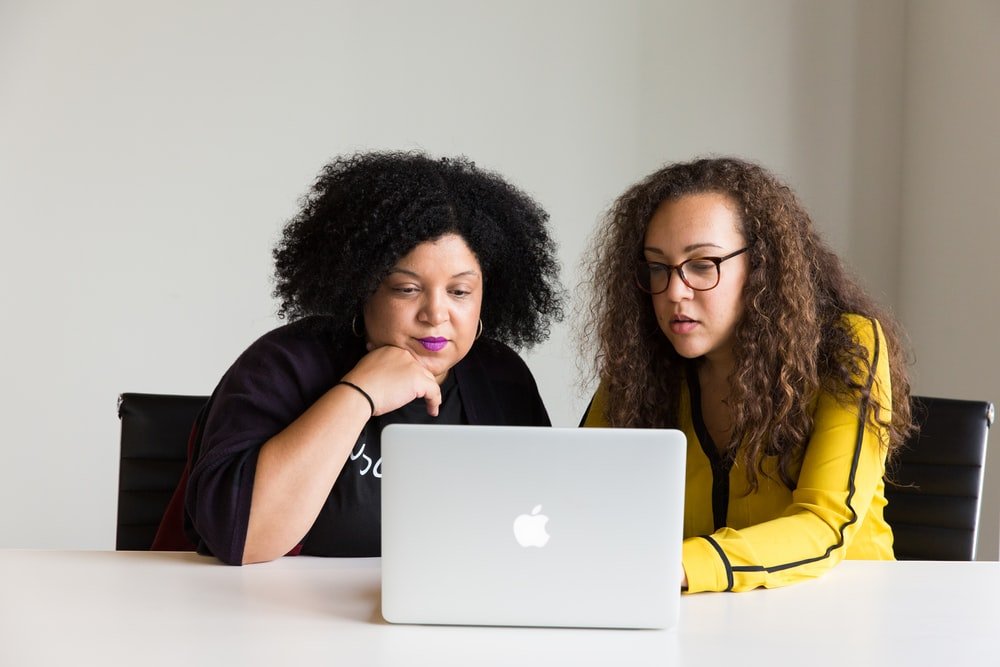 two women looking at the screen of a MacBook