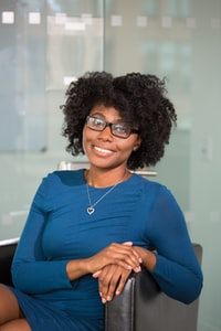 Woman with curly hair and glasses in a blue dress on a chair smiling