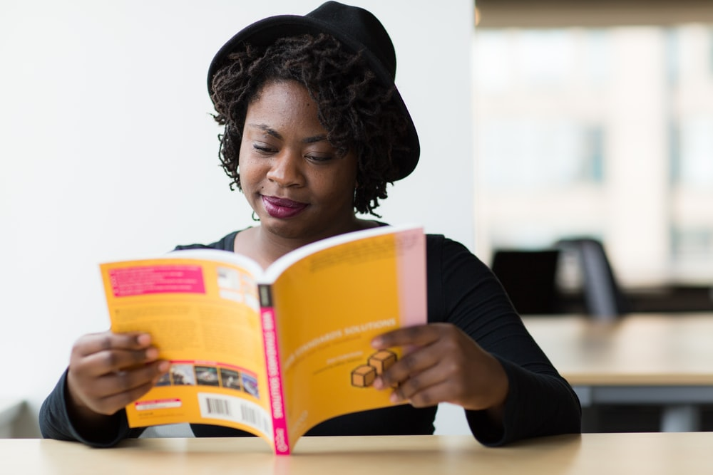 woman smiling and reading book