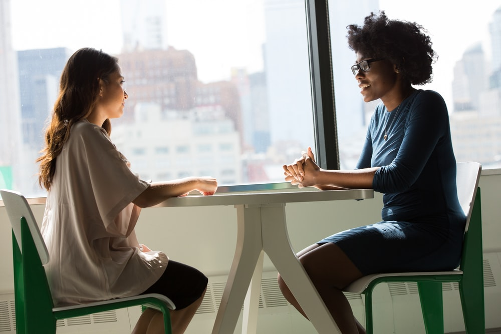 two women sitting beside table and talking