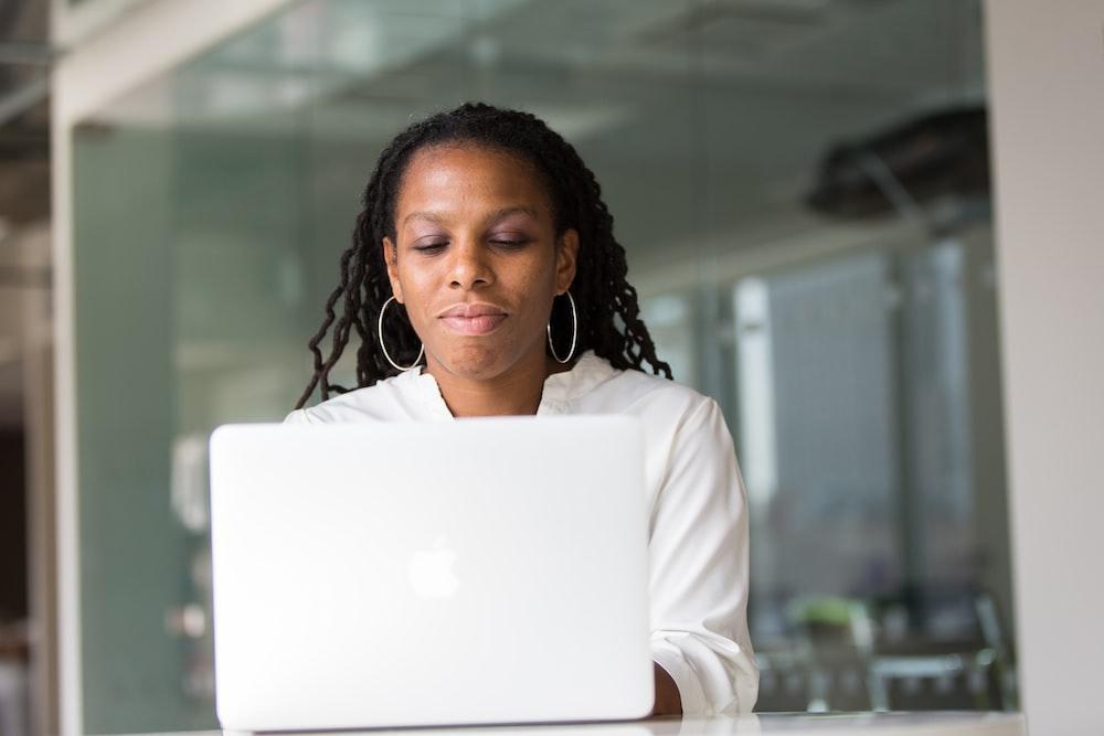 woman wearing white top using MacBook