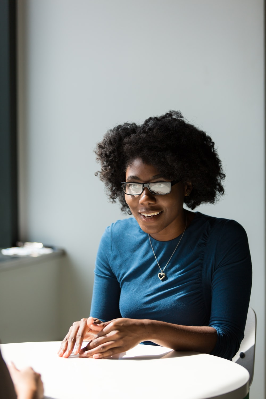 smiling woman wearing blue shirt sitting beside table