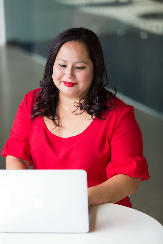 smirking woman wearing red top using laptop computer