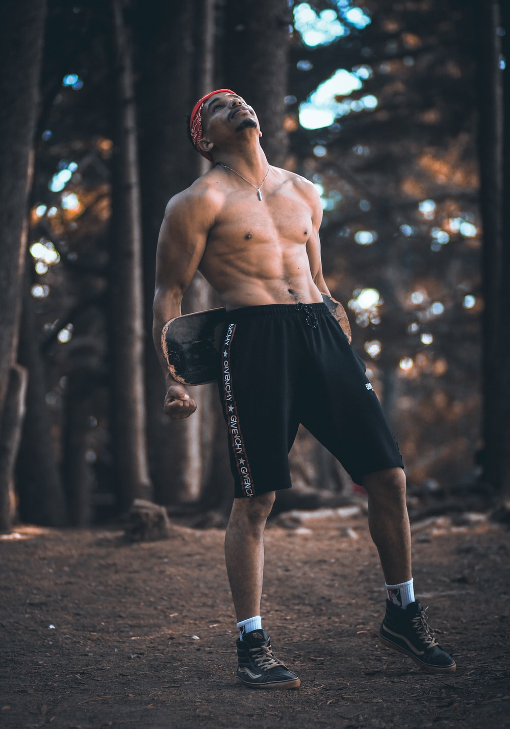 topless man wearing black shorts carrying skateboard