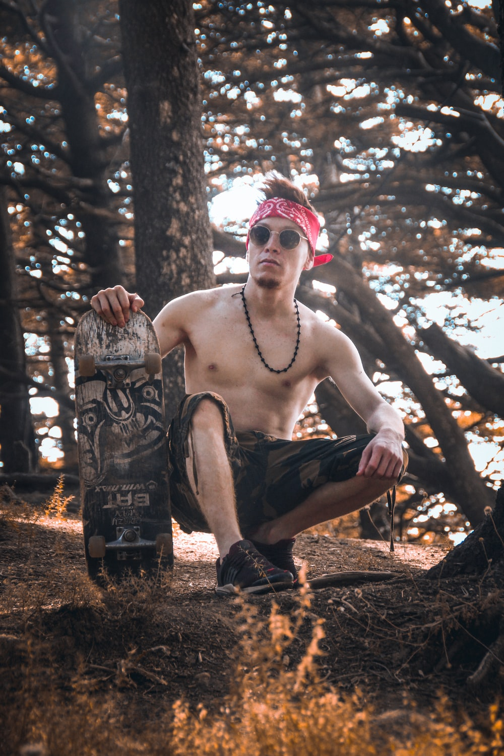 man squatting and holding skateboard near trees