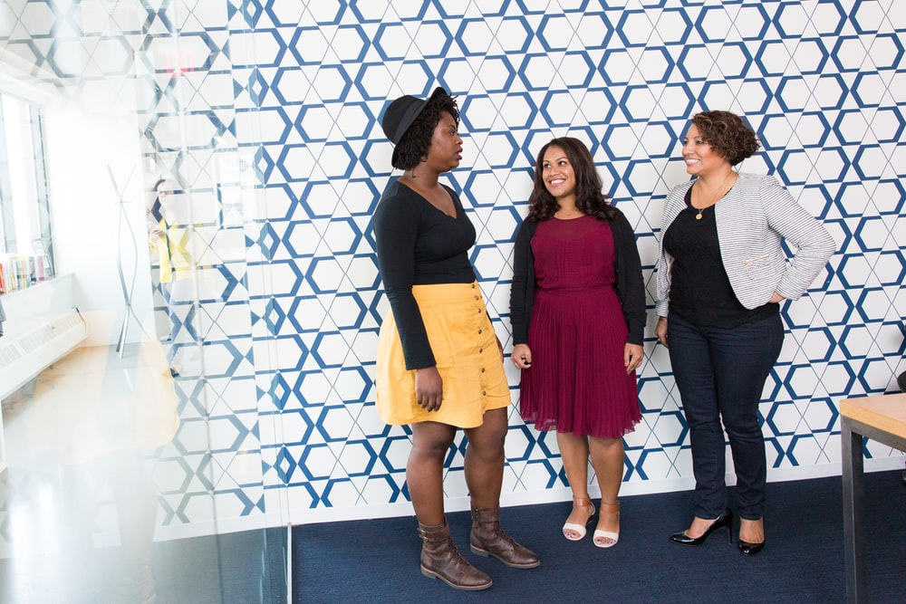 three standing women talking to each other