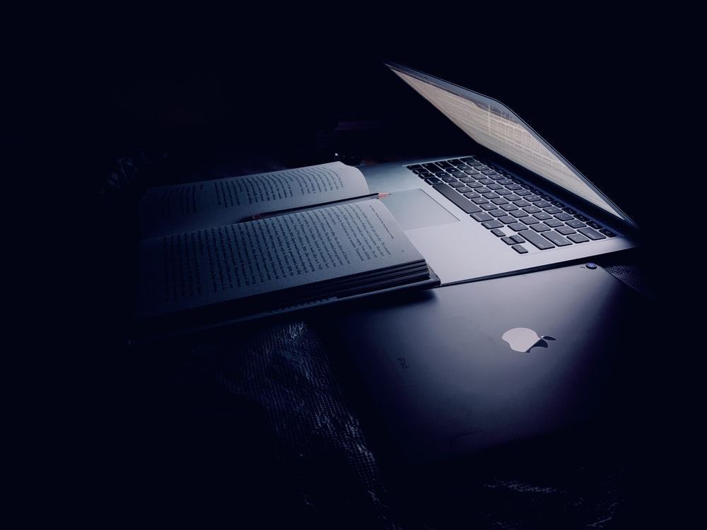 black and gray laptop computer beside book