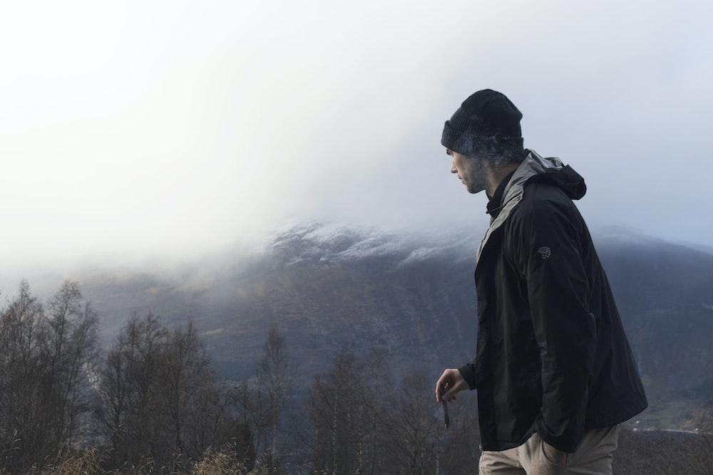 man wearing black jacket looking at mountain