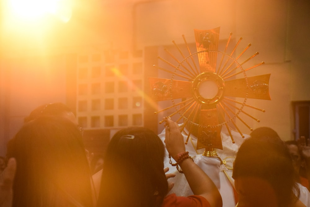 people standing beside gold cross
