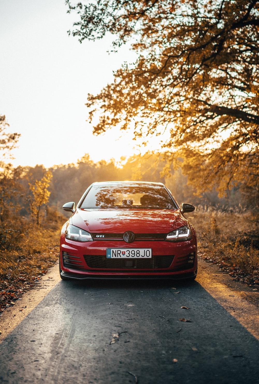 red vehicle beside tree
