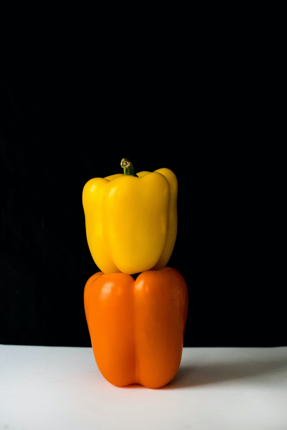 two yellow and orange bell peppers on white surface