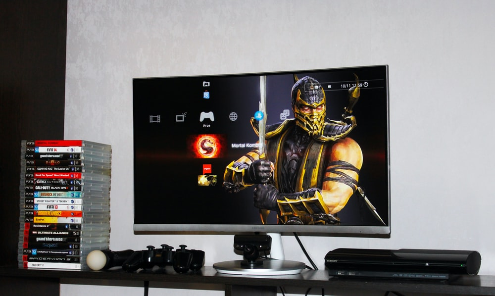 flat screen monitor beside PS3 Super Slim