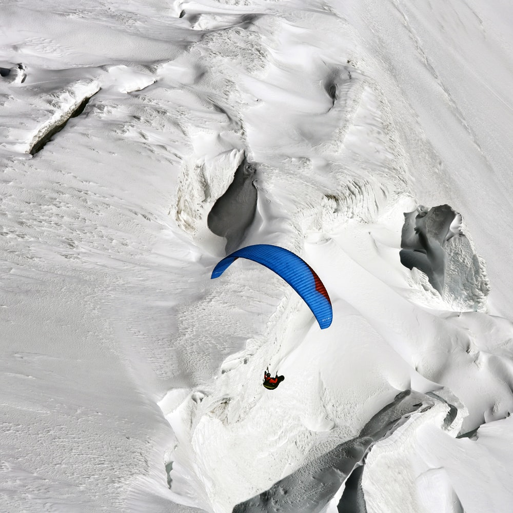 person paragliding over snow hill