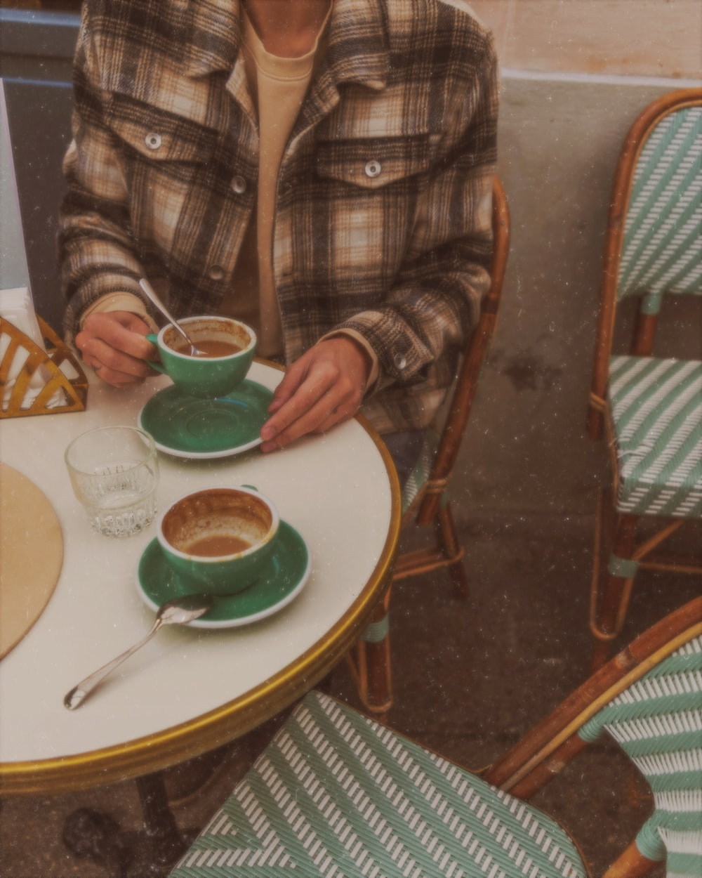 brown and black plaid long-sleeved shirt sitting by the table holding teacup