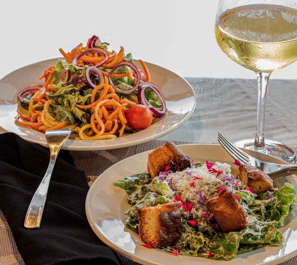 two plate of food beside wine glass