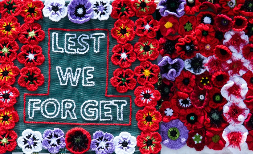 "A tapestry with poppies all over it that says ""lest we forget"" in the middle."