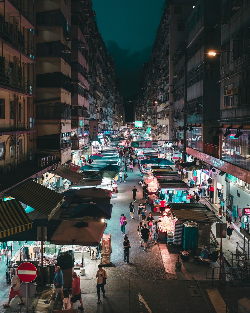 people walking on road near buildings at night time