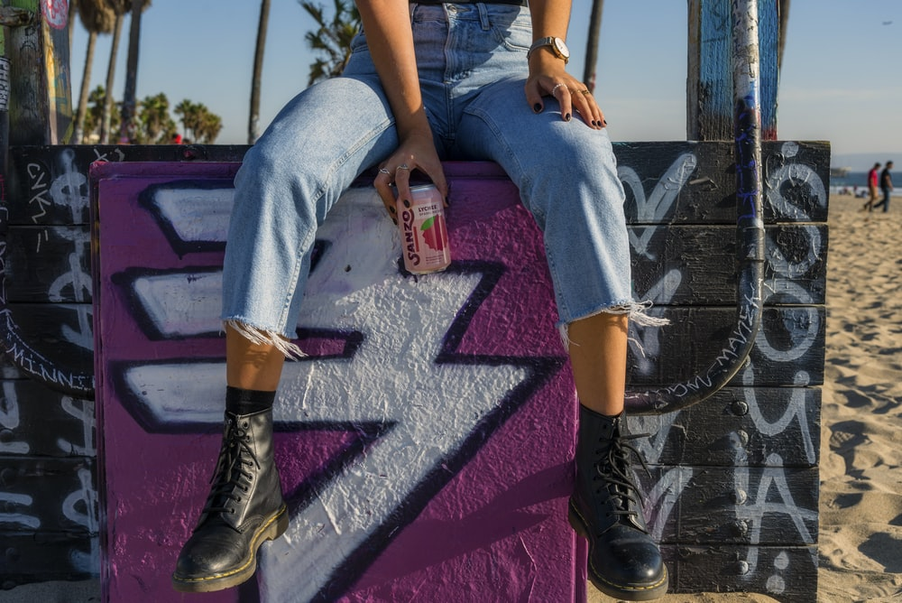 person wearing blue denim jeans holding strawberry soda can