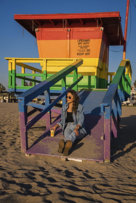 woman wearing blue denim jacket and denim jeans sitting on beach lighthouse