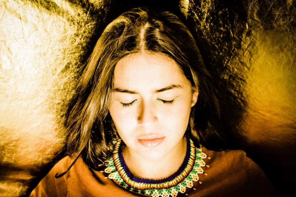 closed eyed woman lying on gold textile