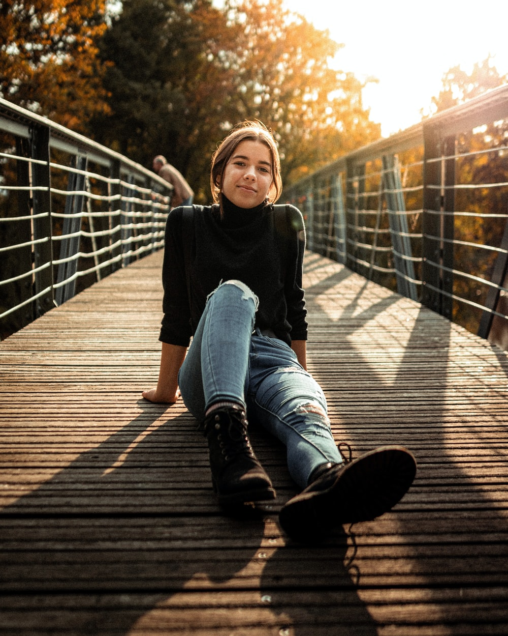 woman in black high-neck sweater and blue jeans sitting on woodn bridge