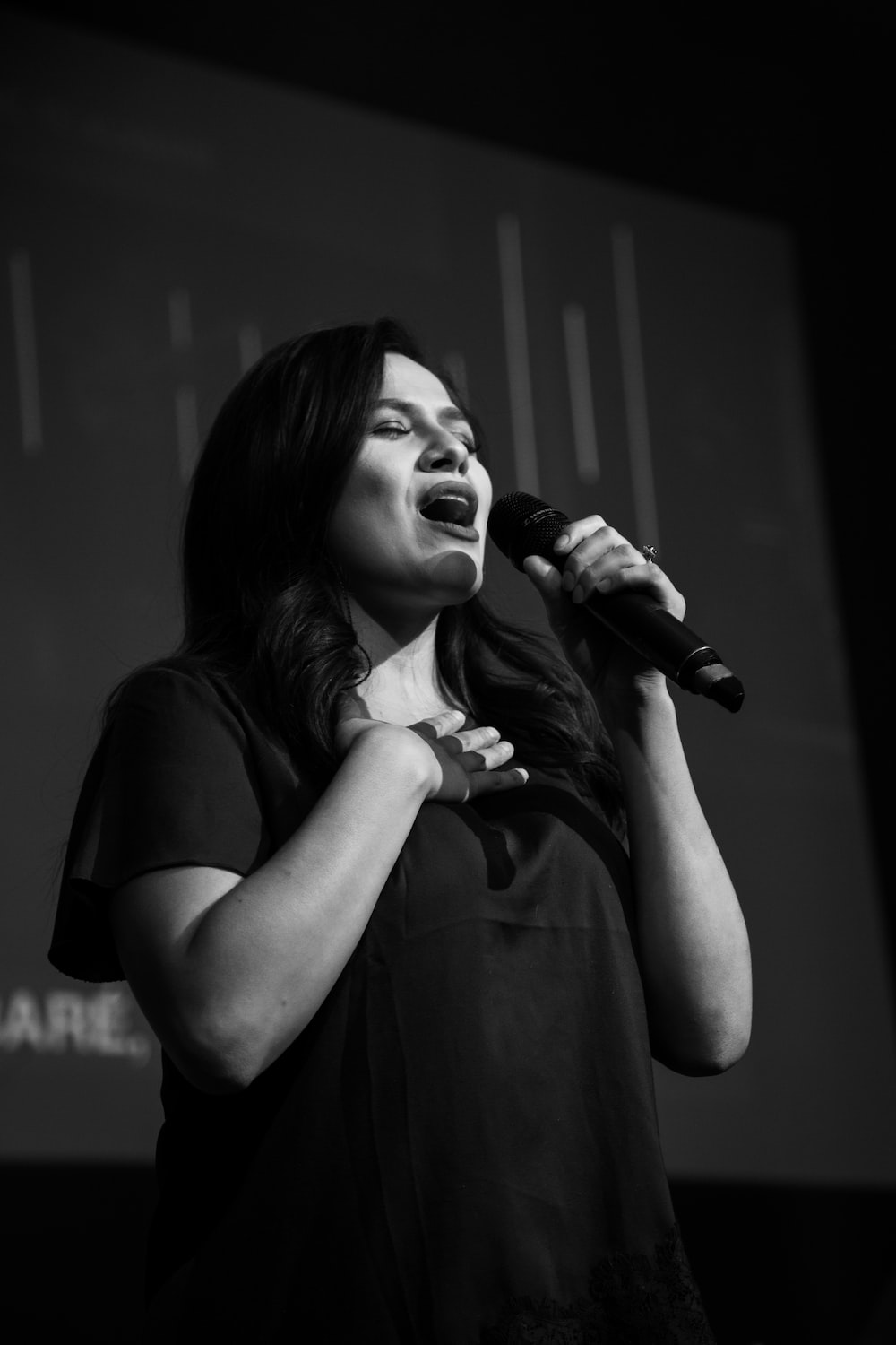 grayscale photography of woman singing