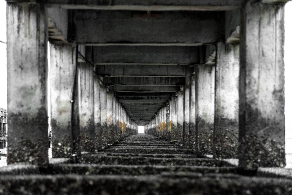 grayscale photography of concrete bridge posts