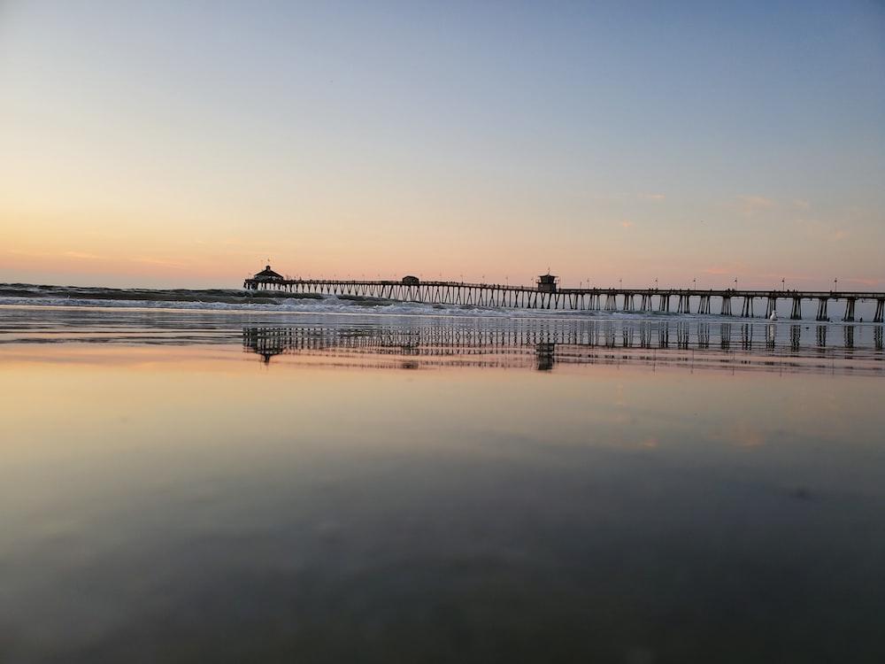 black steel bridge viewing body of water under blue and orange sky