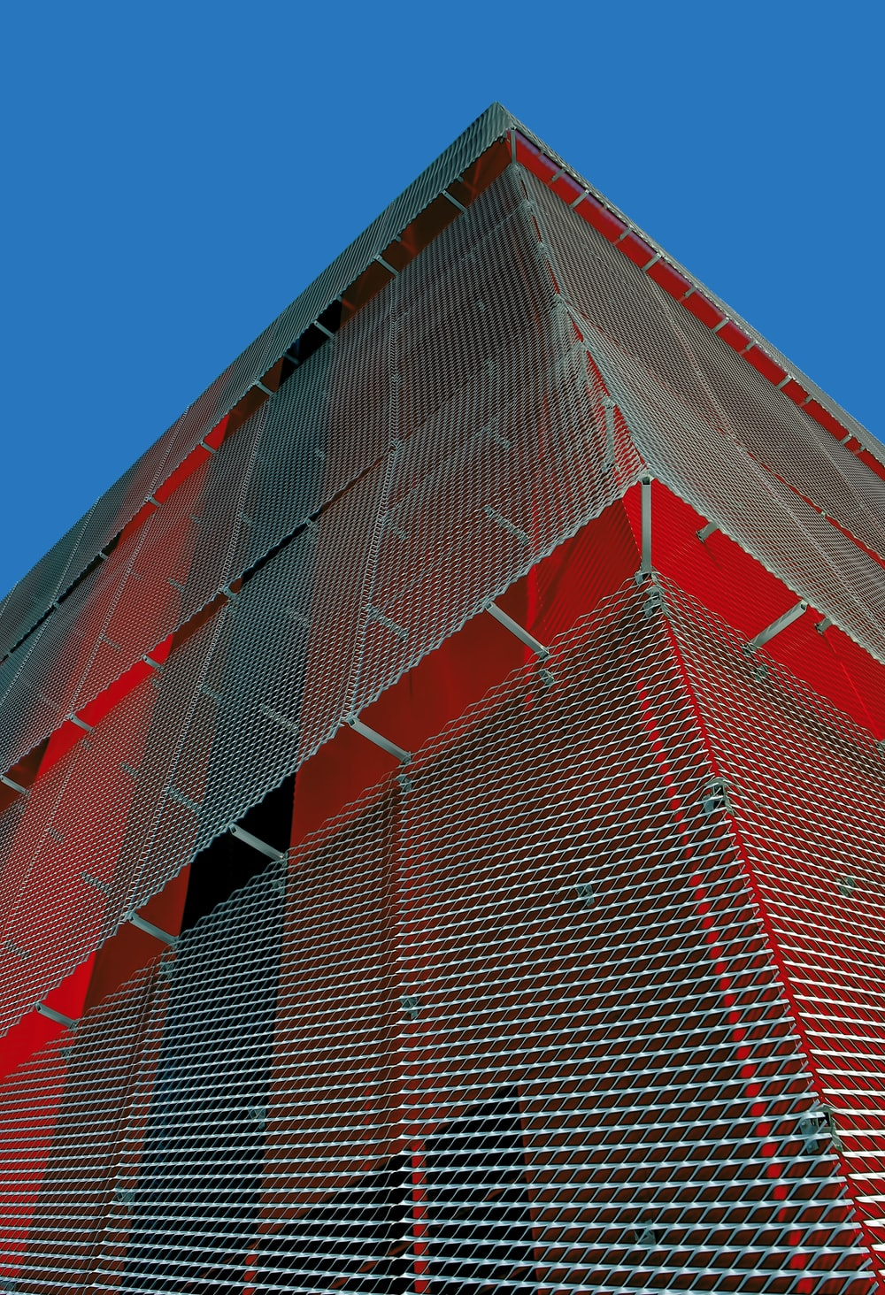 red and gray high-rise building under blue sky