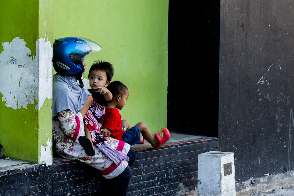 woman wearing helmet sitting while carrying baby and another child sitting