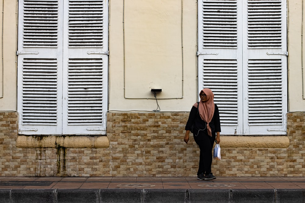 woman wearing beige hijab headscarf standing near building