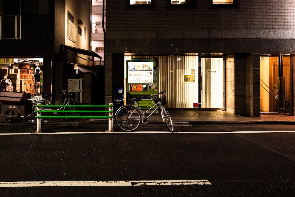 black bike parking near road and raising during night time